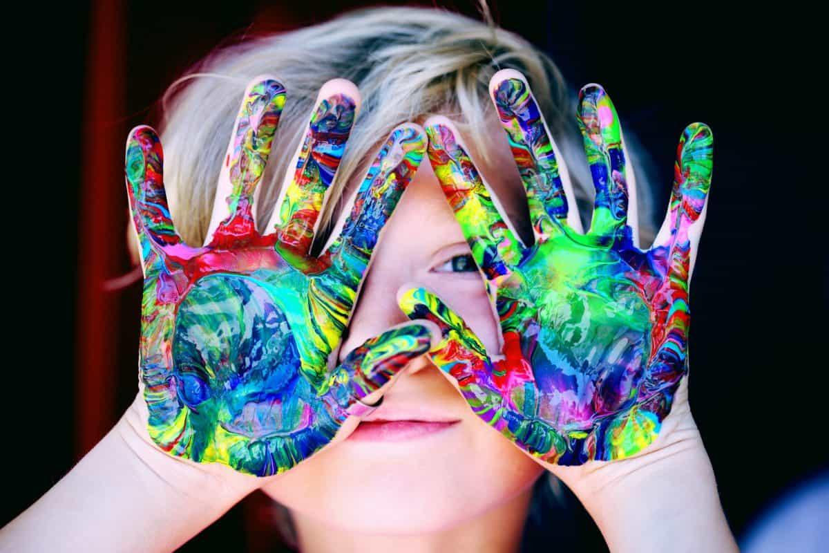 Kind hält bunt bemalte Hände vors Gesicht. Quelle: pexels.com