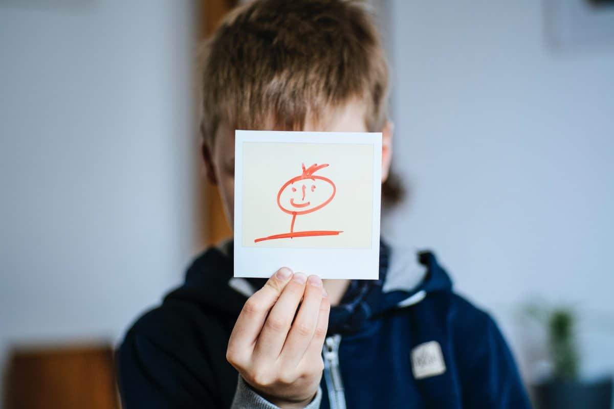Kind hält Polaroid mit Strichmann-Gesicht vors Gesicht. Quelle: pexels.com