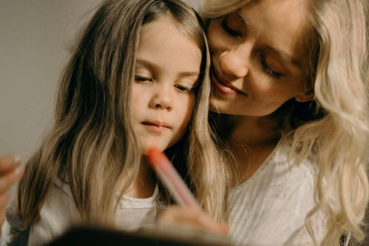 Mutter mit Tochter, die etwas schreibt. Quelle: pexels.com